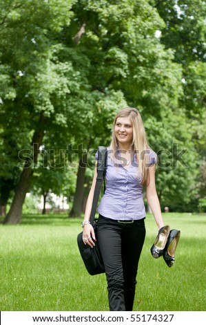Young business woman wit laptop bag walking outdoors in park and holding shoes - stock photo