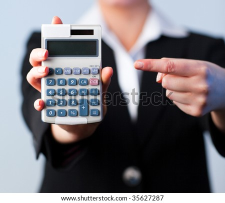 Young Business woman with a calculator with focus on calculator - stock photo