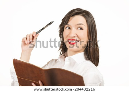 Young business woman with agenda. Thoughtful well dressed businesswoman checking her agenda, studio shot on white background - stock photo