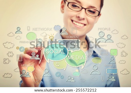 Young business woman with eyeglasses drawing social media concepts - stock photo