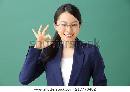 young business woman with glasses against green background - stock photo