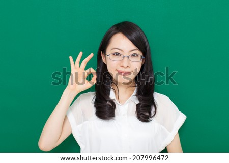 young business woman with glasses showing OK gesture, against green background  - stock photo