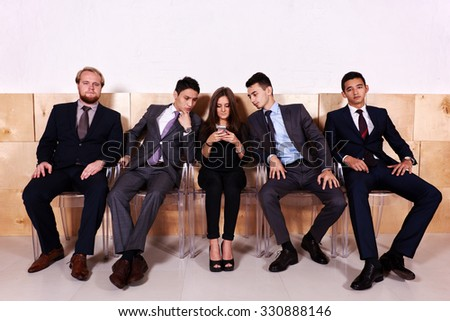 Young business woman with her partners reading text on mobile phone while they waiting for the meeting, successful female financier chatting on cell telephone while sitting in hallway big company  - stock photo