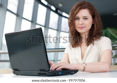 Young business woman with laptop at cafe