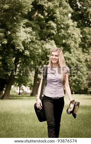 Young business woman with laptop bag walking outdoor in park and holding shoes - stock photo