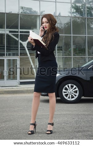 Young business woman with long hair on phone standing in the street background car