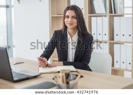 Young business woman with notebook in the office, workplace. - stock photo