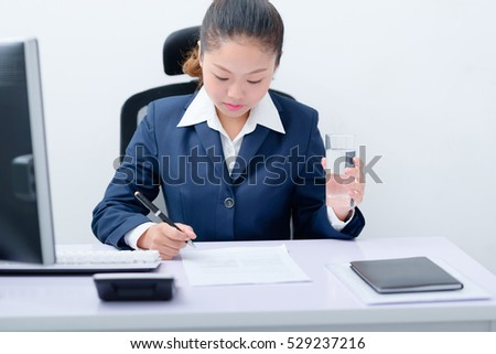 Young business woman working at desk.