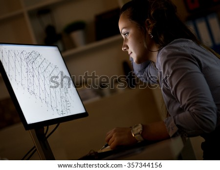 Young business woman working late in office.She works late into the night looking at monitor. - stock photo