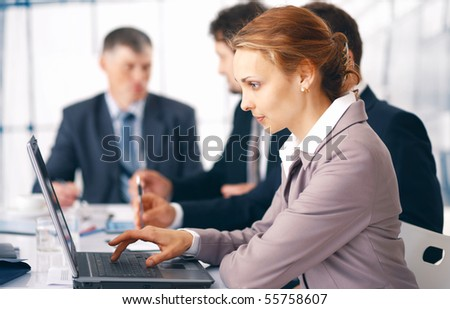 Young business woman working on her laptop with her colleagues at the background. - stock photo