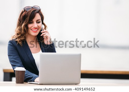 Young business woman working on laptop and talking on mobile phone - stock photo