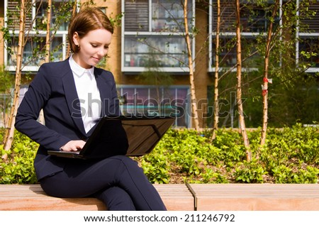 Young business woman working on laptop outdoors. - stock photo