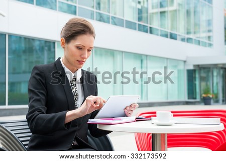 Young business woman working on tablet portrait in a modern background