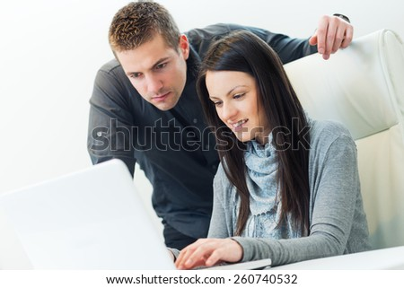 Young business woman working together with her colleague on laptop in office - stock photo