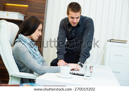 Young business woman working together with his colleague on laptop in office - stock photo