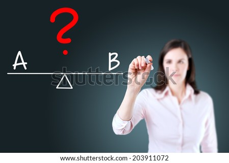 Young business woman writing A and B compare on balance bar. Blue background. - stock photo