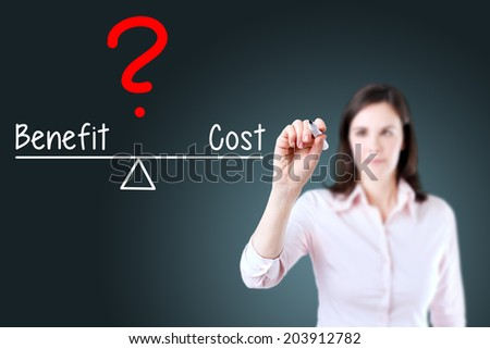 Young business woman writing cost and benefit compare on balance bar. Blue background. - stock photo