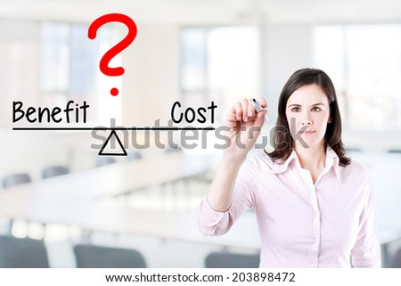 Young business woman writing cost and benefit compare on balance bar. Office background - stock photo