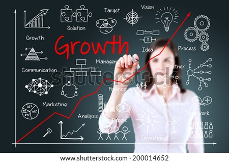 Young business woman writing growth graph. Blue background.