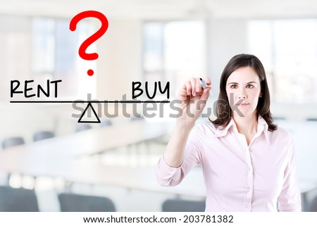 Young business woman writing rent and buy compare on balance bar. Office background. - stock photo