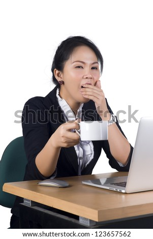 Young business woman yawning at her desk with a cup of coffee, Model is Asian woman. - stock photo