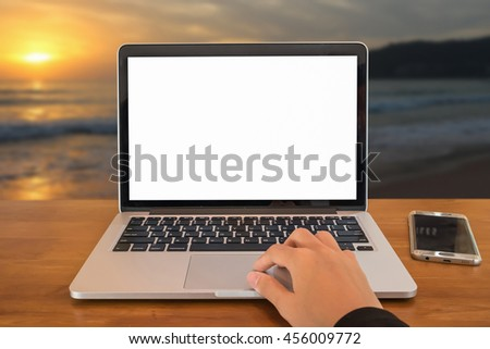 Young business women hand using laptop computer and smartphone outdoor office with sunset background, blank screen. - stock photo