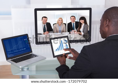 Young Businessman Analyzing Graph While Chatting With His Colleagues - stock photo