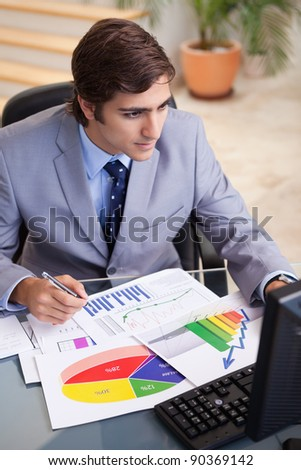 Young businessman analyzing statistics at his desk - stock photo