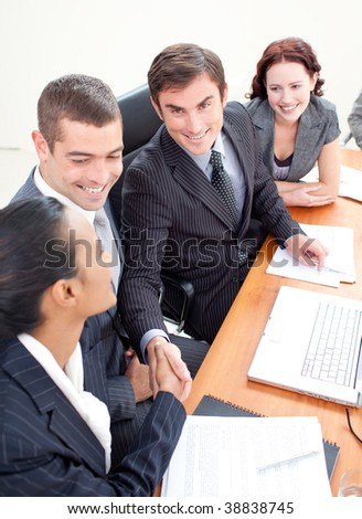 Young businessman and businesswoman in a meeting shaking hands - stock photo