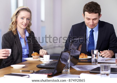 Young businessman and businesswoman sitting at conference table have a break during meeting - stock photo
