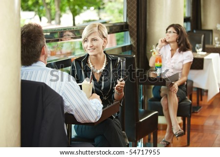 Young businessman and businesswoman talking in cafe.