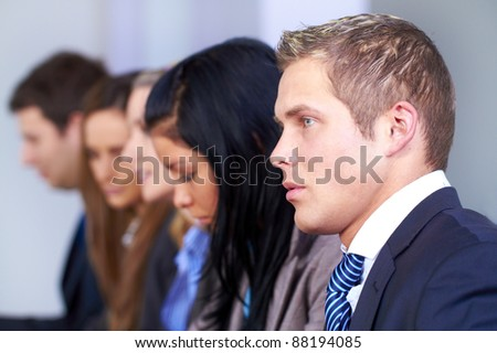 Young businessman and his team of 4 people sitting at conference table - stock photo