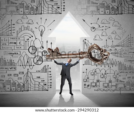 Young businessman and keyhole at background lifting big key above head - stock photo