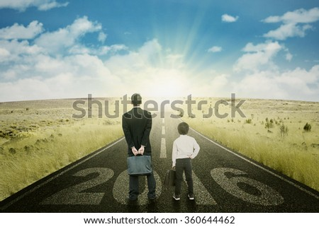 Young businessman and little boy standing on the road with numbers 2016 - stock photo