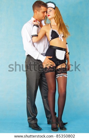 Young businessman and parlormaid in loving embrace on blue background - stock photo