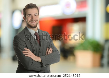 Young Businessman at the airport with his arms crossed - stock photo