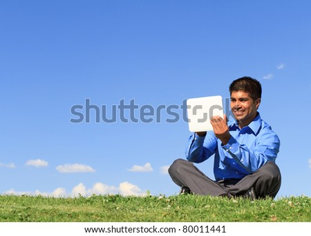 young businessman at the park working with tablet - stock photo