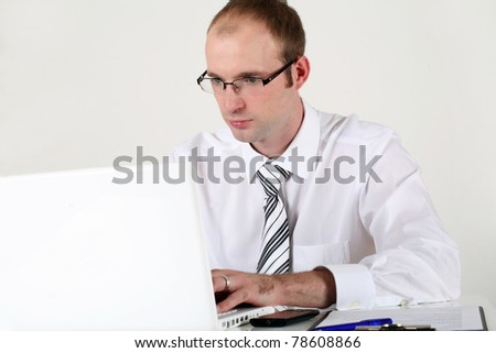 Young businessman at working on computer and thinking