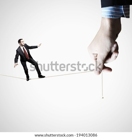 Young businessman balancing on rope controlled by male hand