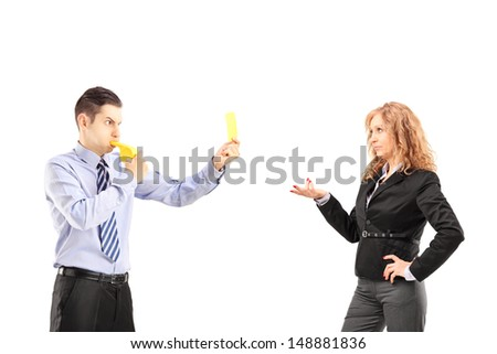 Young businessman blowing a wistle and showing a yellow card to his female colleague, isolated on white background - stock photo