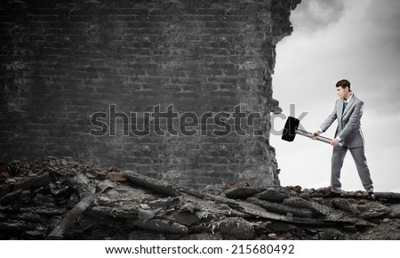 Young businessman breaking old wall with hammer - stock photo