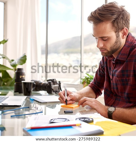 Young businessman busy taking notes on a note pad, sitting at his glass desk in his home office with his morning coffee - stock photo