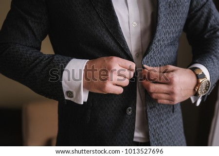 young businessman buttoning his jacket. Gatherings of the groom on his wedding day