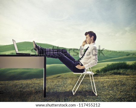 Young businessman calling. in a large grace field, with his feet on his desk - stock photo