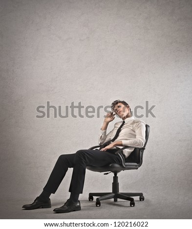 Young businessman calling lying on a chair