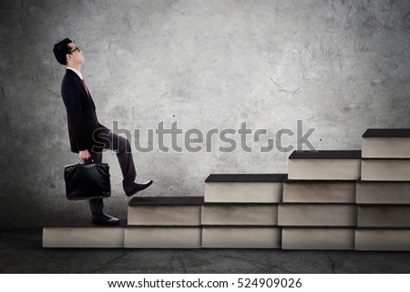 Young businessman carrying a briefcase and walking upward on the books stair