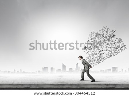 Young businessman carrying his great business plan on back - stock photo