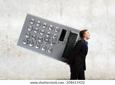 Young businessman carrying huge calculator in hands - stock photo