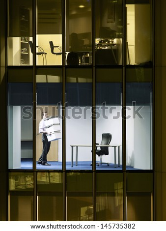 Young businessman carrying stack of boxes in office at late night - stock photo