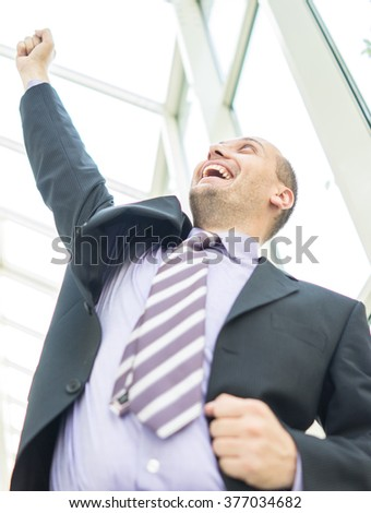 Young businessman celebrating in office building